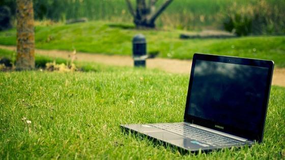 Bærbar PC som står ute på en veldig grønn gressplen