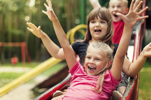 Glade barn sklir på sklie