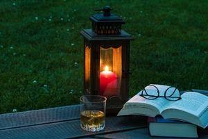 bildet forestiller en lykt, en stabel bøker og et glass med drikke