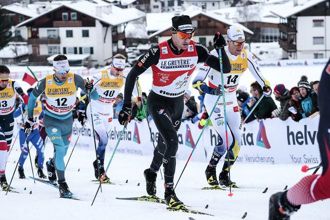 DARIO COLOGNA säkrade sig ett perfekt utgångsläge inför avslutningen av Tour de Ski. Daniel Richardsson (bakom) var stark 6:a i masstarten i Val di Fiemme, medan Oskar Svensson (bak till vänster) var näst bäste svensk som 16:e man. Foto: NORDIC FOCUS