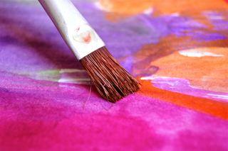 Bildet viser et abstrakt maleri i toner av lilla og rosa, med en malepensel i forgrunnen