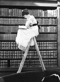 bildet viser en dame som sitter på toppen av en stige og leser en bok