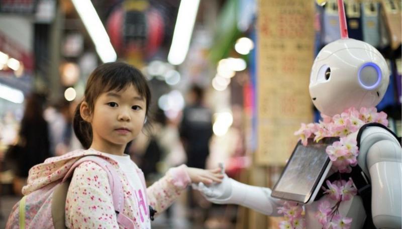 Liten jente hilser på robot.
