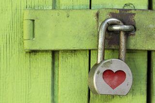 bildet viser en hengelås med hjertemotiv mot en grønn bakgrunn