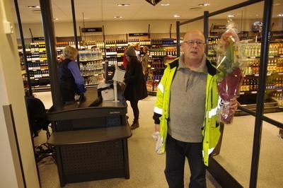 Førse kunden, Arne Eri, i det nye vinmonoplet i Ås sentrum med blomsten han fikk