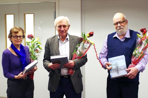 Reidun Aalerud, Halvor Holtestaul og Øystein Retvedt fra bygdebok ressursgruppa får blomster og bok i forbindelse med lanseringen av boka i Ås bibliotek.