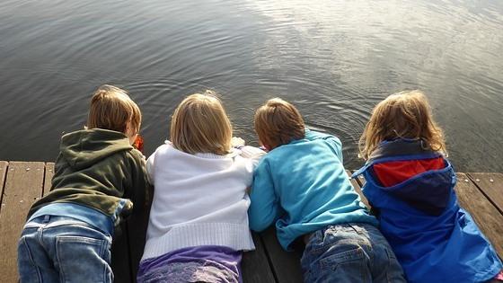 Barn som ligger på en brygge og ser ut på vannet
