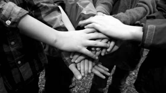 Fotografi av mange som holder hendene oppå hverandre