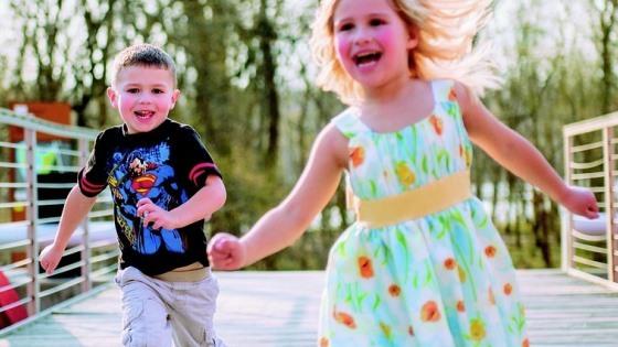 Fotografi av gutt og jente som løper