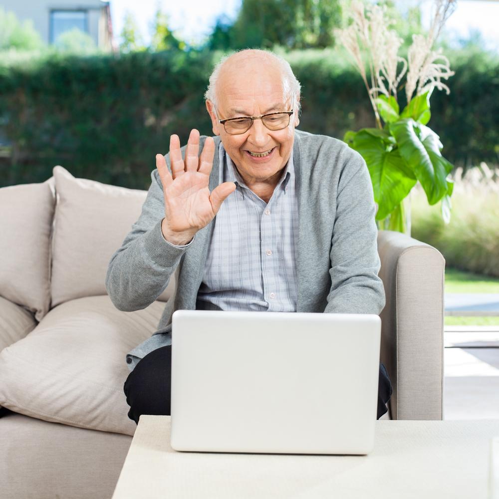 Fornøyd eldre mann bruker PC med videokommunikasjon