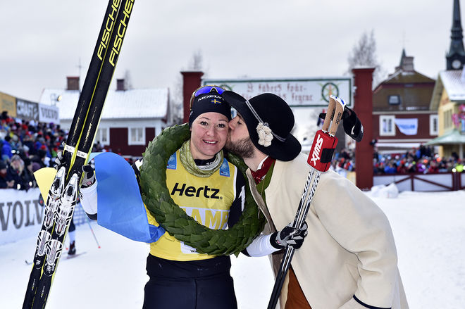 BRITTA JOHANSSON NORGREN får en välförtjänt segerpuss av kransmasen Linus Rapp. Foto: NISSE SCHMIDT/Vasaloppet