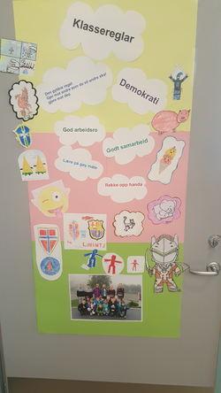 Klassereglane våre heng på døra i klasserommet