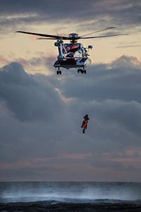 Bilde redningsmann henger under redningshelikopter