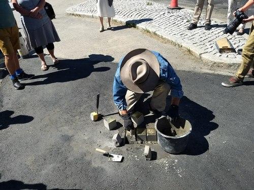 Fotografi av kunstneren Gunter Demnig som legger ned steinene i asfalten.