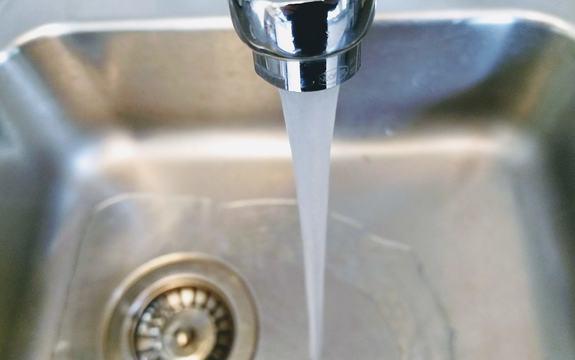 Fotografi av vannkran med rennende vann