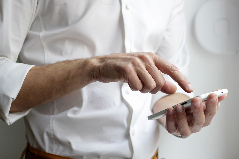 Illustrasjon foto av mann i hvit skjorte som holder telefon