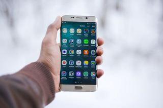 En hånd holder en mobiltelefon med apper
