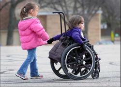Et barn hjelper et barn i rullestol