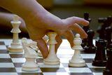 En barnehånd flytter sjakkbrikke