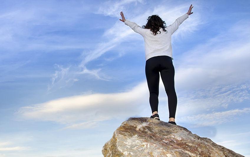 Dame på toppen av et fjell som strekker ut armene.