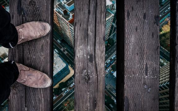 Illustrasjonsfoto angst, en mann balanserer på planker høyt oppe over bakkenivå.