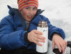 Barn med termos ute på vinteren
