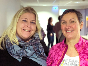 To smilende kvinner i korridor med kursdeltakere i bakgrunnen