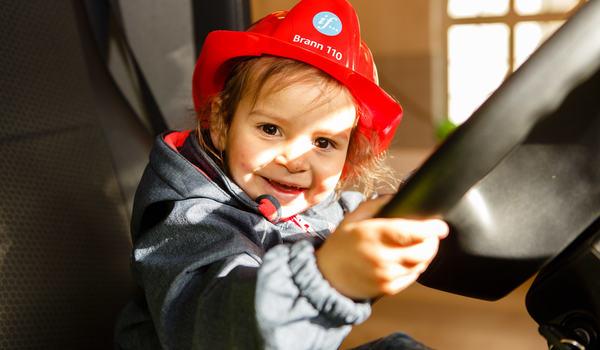 Lite barn som sitter bak rattet i en brannbil.
