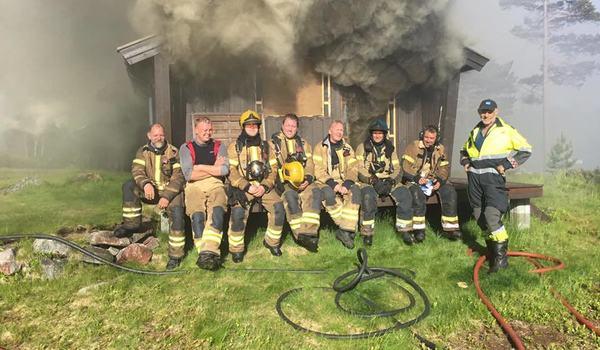 Brannmenn utenfor en hytte som brenner ned