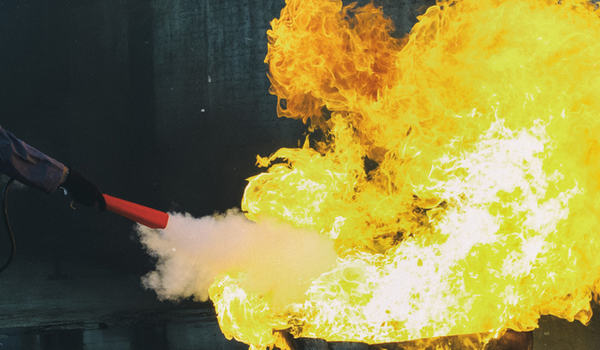 Kvinne som slukker brann i tønne