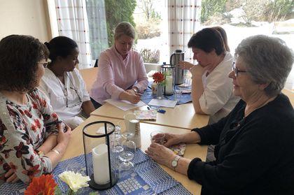 Fem mennesker snakker sammen rundt et bord.