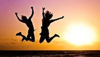 glad ungdom hopper i solnedgang