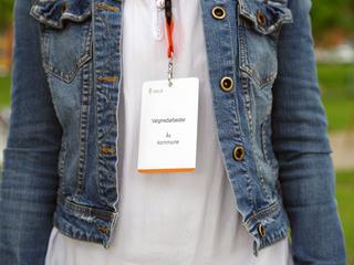 Foto som viser en person med Valgmedarbeider-kort rundt halsen