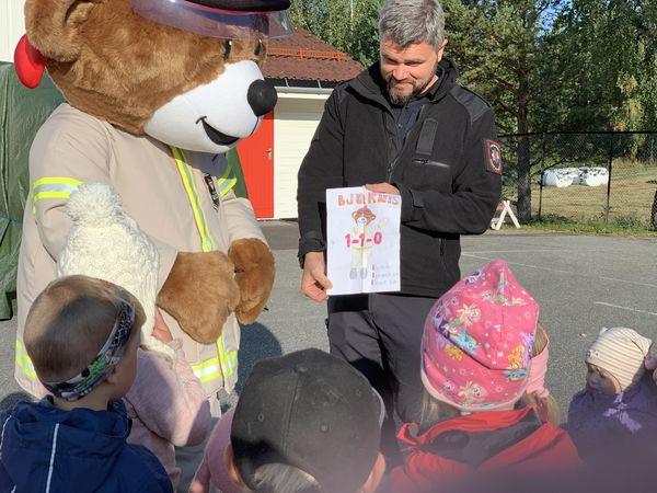 Brannbamsen Bjørnis og brannmann Per Ansgar Østby snakker til barn i Bjørklund barnehage
