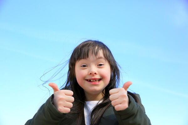 Portrait of little girl smiling on background of the blue sky