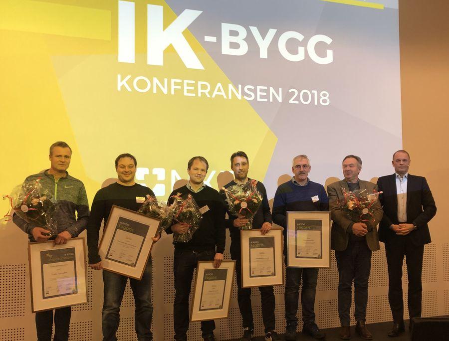 PRISDRYSS: Under konferansen deles IK-byggprisen i gull og sølv. Her er vinnerne av IK-byggprisen i 2018 samlet på scenen. Foto: Sindre Haarr