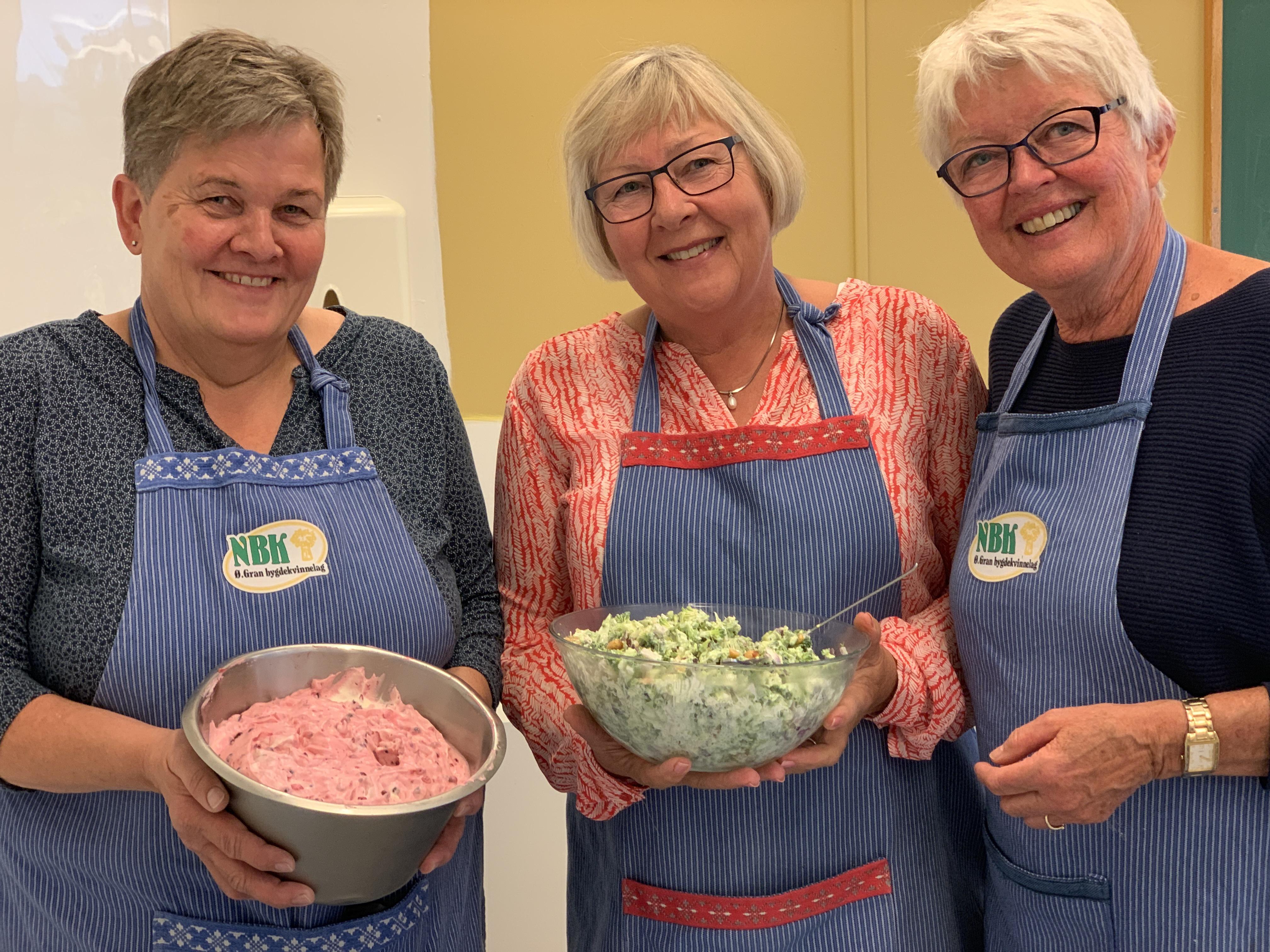 Tre damer fra bygdekvinnelaget holder opp en bolle med trollkrem og en bolle med brokkolisalat.