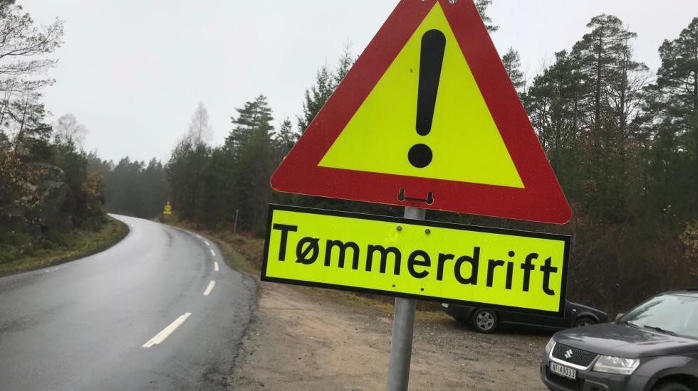 """Fotografi av varselskilt med """"Tømmerdrift"""" langs veien."""