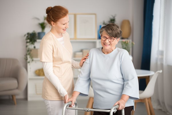 Hjemmetjenesteansatt bistår eldre kvinne med gåstol hjemmme
