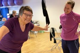 Dame trener styrke med ringer som henger fra taket, mens en kvinnelig fysioterapeut står ved siden av og følger med.