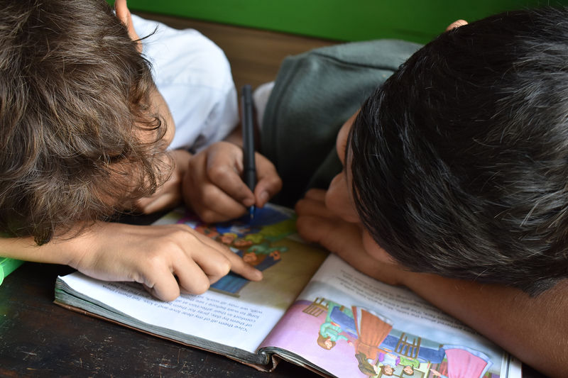 To gutter gjør lekser sammen på skolen