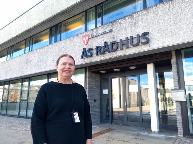 En kvinne, kommuneoverlegen i Ås, står foran et grått bygg med logoen Ås Rådhus på.