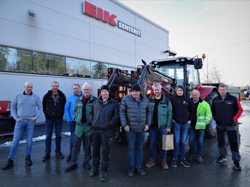 En gjeng med menn står foran en traktor utenfor Eiksenteret på Jaren.