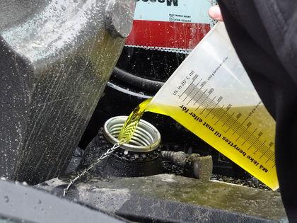 Dieseltanken på en traktor blir fylt opp med diesel fra et målebeger.