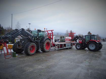 En traktor med tilhenger står stille, mens en annen traktor løfter en rundball opp på tilhengeren.
