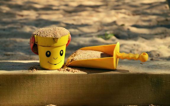 Illustrasjonsbilde: En spade og en liten kopp med sand på kanten av en sandkasse.