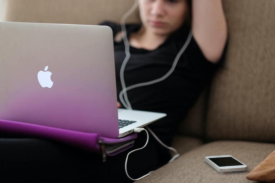 Ungdom i sofa med PC, telefon og ørepropper