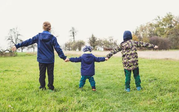 Tre barn holder hender ute på gresset.