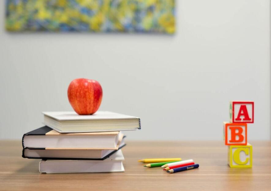 Bildet viser epler på en bunke bøker, ved siden av klosser med ABC.