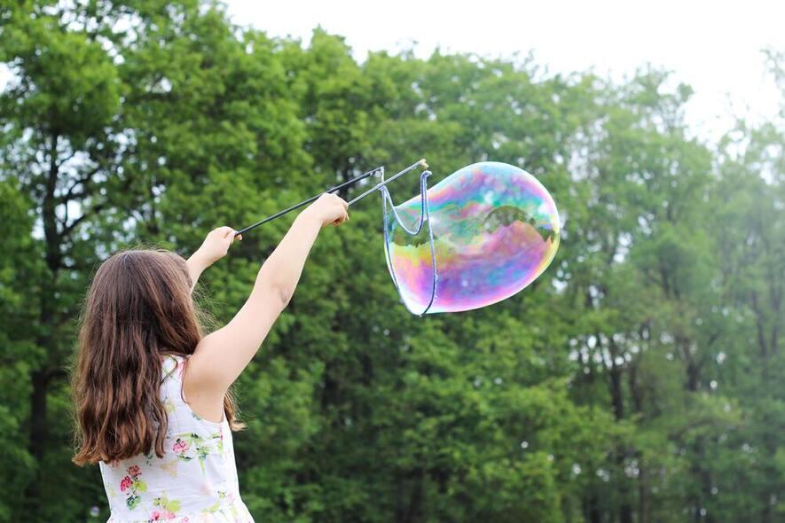 Foto av en jente som blåser en stor såpeboble